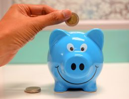 Blue piggy bank with hand inserting coin
